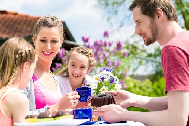 Família tomando café no jardim comendo bolo
