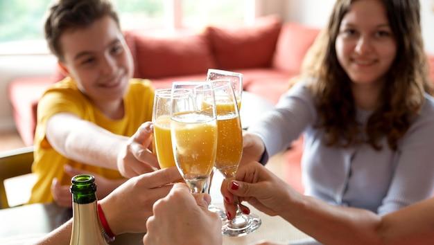 Família torcendo com taças de champanhe em casa