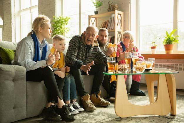 Família torcendo e assistindo tv em casa na sala de estar