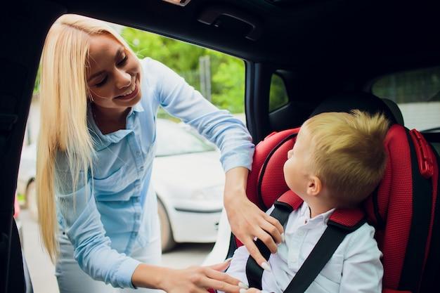 Família, transporte, viagem por estrada e conceito dos povos - criança feliz que prende a criança com cinto de segurança no carro