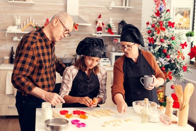 Família usando cortador de formas para massa no dia de natal