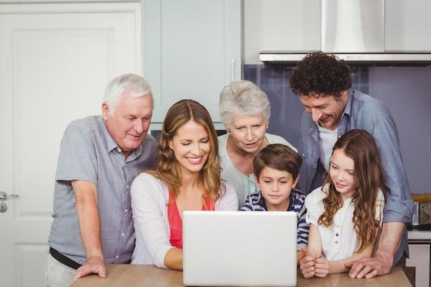 Família usando laptop na cozinha