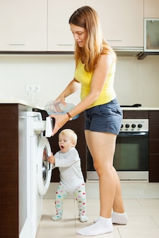 Família usando máquina de lavar roupa com roupa