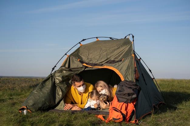 Família usando máscaras e sentada em uma barraca com seu cachorro