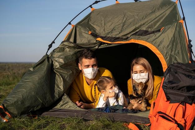 Família usando máscaras e sentada na barraca com a vista frontal do cachorro