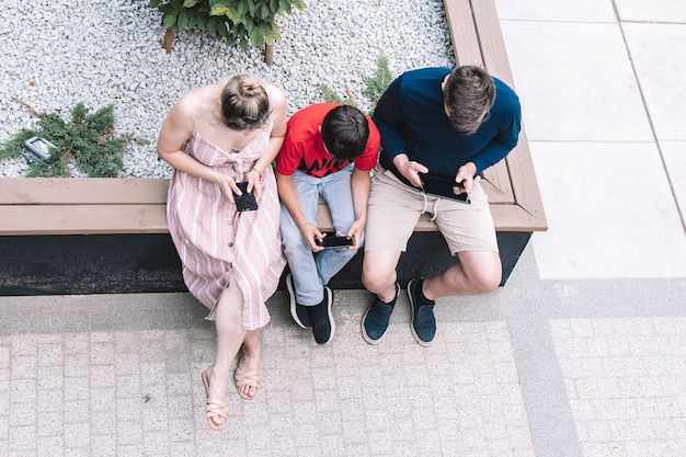 Família usando novas tecnologias ao ar livre em dia de verão. estilo de vida. foto de alta qualidade.