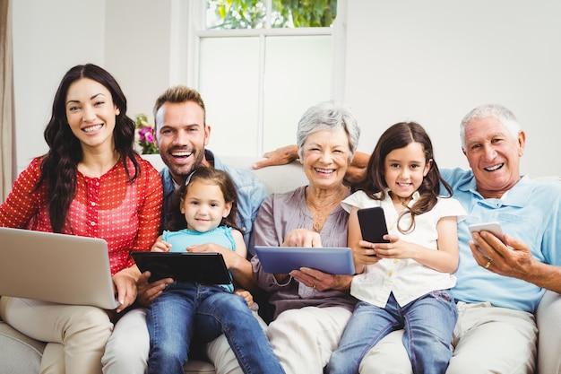 Família usando tecnologias enquanto está sentado no sofá