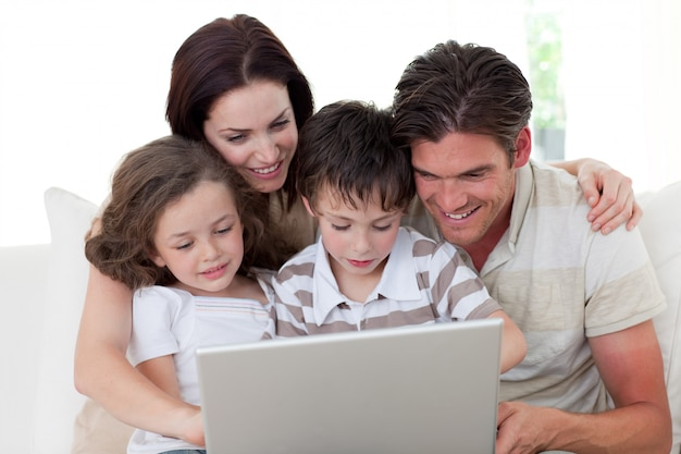 Família usando um laptop no sofá