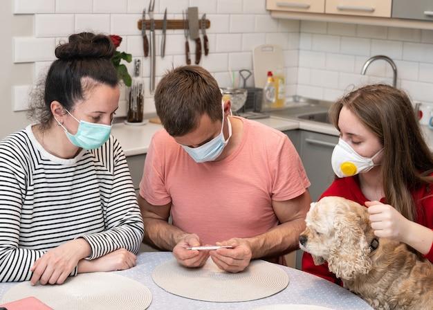 Família verificando a temperatura durante a pandemia de covid-19 em casa