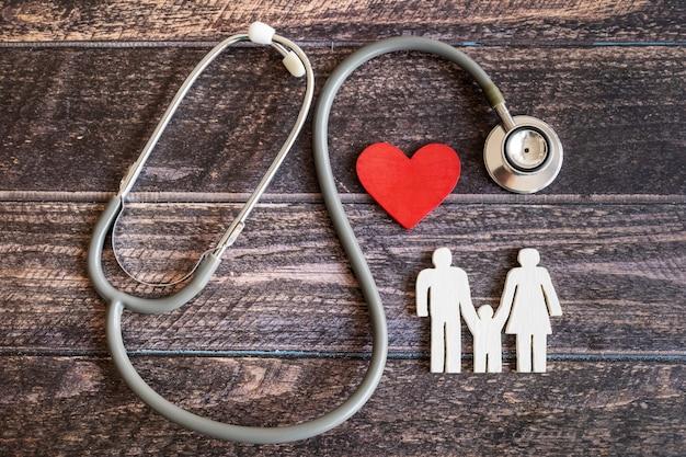 Família vermelha de coração, estetoscópio e ícone na mesa de madeira. conceito de seguro médico