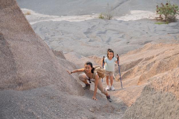 Família viagens-alpinistas com mochila, olhando para a montanha, mãe com filho na hora do dia.