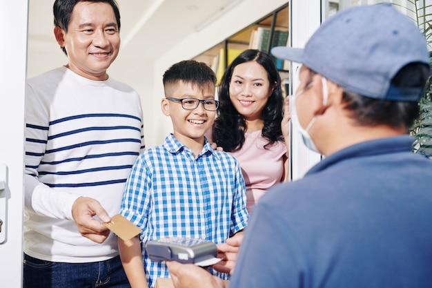 Família vietnamita alegre recebendo pacote e pagando pela entrega