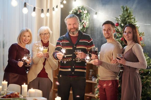 Familiares alegres com luzes cintilantes de bengala aproveitando a festa de natal em casa com a árvore de natal