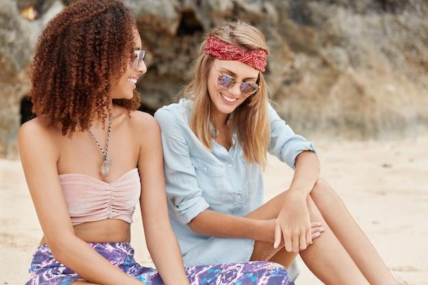 Famílias homossexuais sentam-se lado a lado, têm conversas agradáveis, planejam suas ações nos próximos fins de semana, passam o tempo livre na praia contra o penhasco. casal de mulheres multiétnicas se divertindo ao ar livre