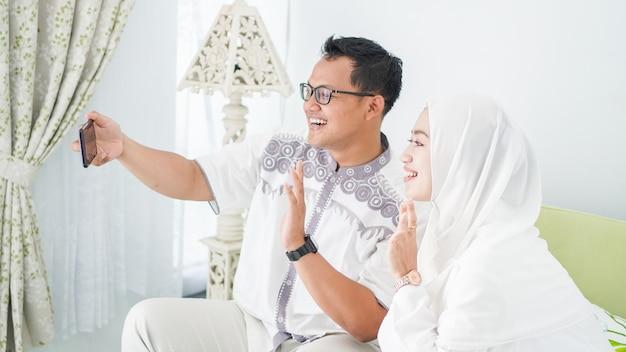 Famílias muçulmanas asiáticas celebram o eid juntas durante videochamadas