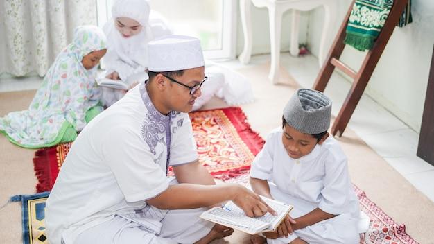 Famílias muçulmanas asiáticas leem o alcorão após as orações