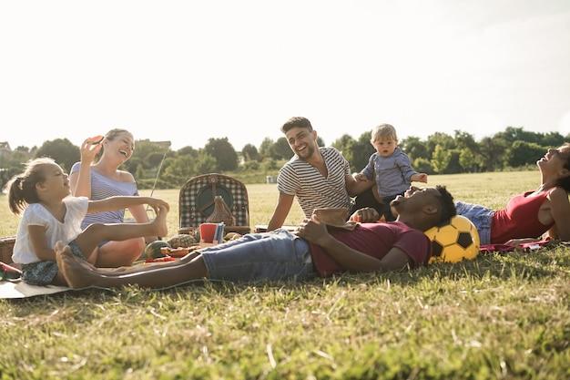 Famílias multirraciais felizes fazendo piquenique ao ar livre no parque da cidade durante as férias de verão - foco principal criança menino