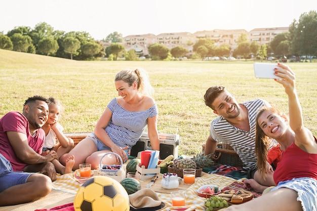 Famílias multirraciais felizes se divertindo fazendo selfie em uma festa de piquenique ao ar livre no parque da cidade - foco principal no rosto da mulher no centro