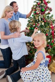 Family pendurado decorações em uma árvore de natal