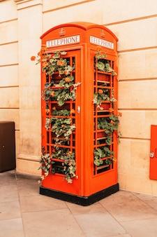 Famosa cabine telefônica vermelha em londres com folhas