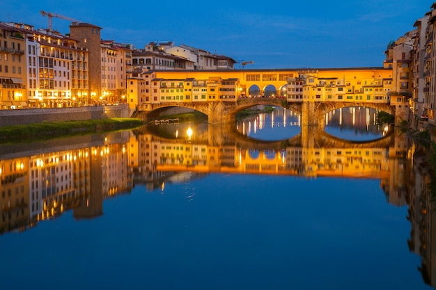 Famosa ponte ponte vecchio sobre o rio arno à noite, florença, itália