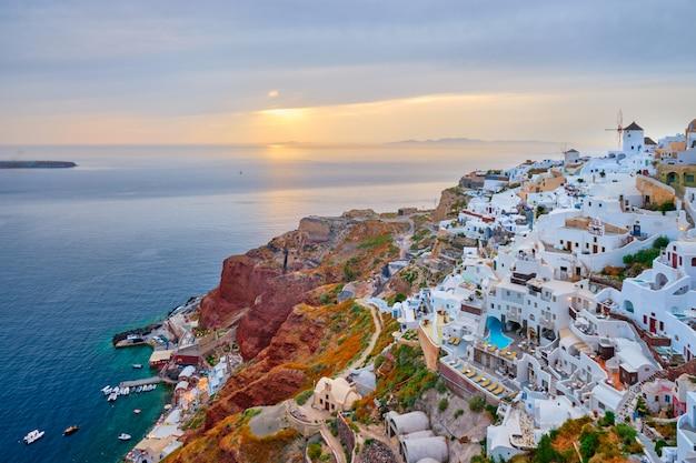 Famoso destino de turista icônico grego selfie vila de oia com casas brancas tradicionais e moinhos de vento na ilha de santorini no pôr do sol no crepúsculo, grécia