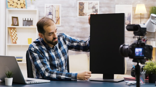 Famoso vlogger filmando a análise do monitor lcd para seus seguidores. criador de conteúdo criativo.