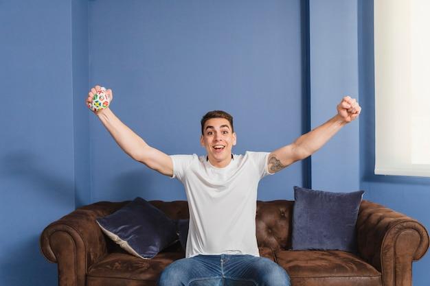 Fan de futebol, levantando os braços no sofá