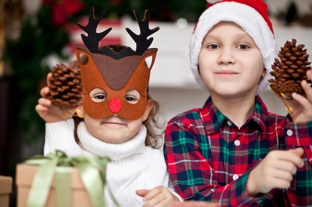 Fanny kids, menina com máscara de veado e menino com chapéu de papai noel