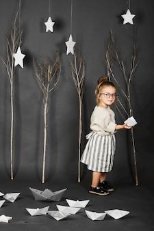 Fanny menina com óculos no fundo cinza com estrelas, árvores e barcos de papel