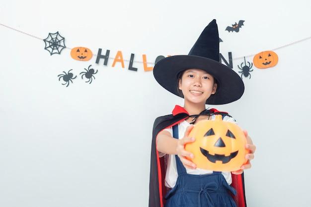 Fantasia de bruxa menina asiática brincando na sala feliz dia das bruxas