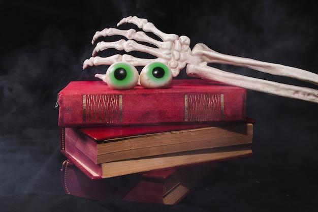 Fantasia de olhos com mão de esqueleto com pilha de livro