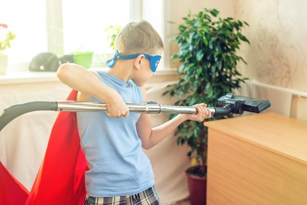 Fantasia de super-herói menino brincando é limpando a casa