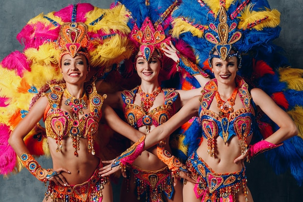 Fantasia de três mulheres no samba brasileiro de carnaval com plumagem de penas coloridas