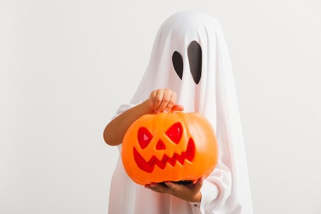 Fantasia infantil de halloween como fantasma com abóbora