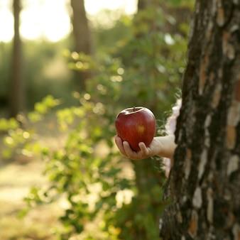Fantasia menina segurando uma maçã vermelha na floresta