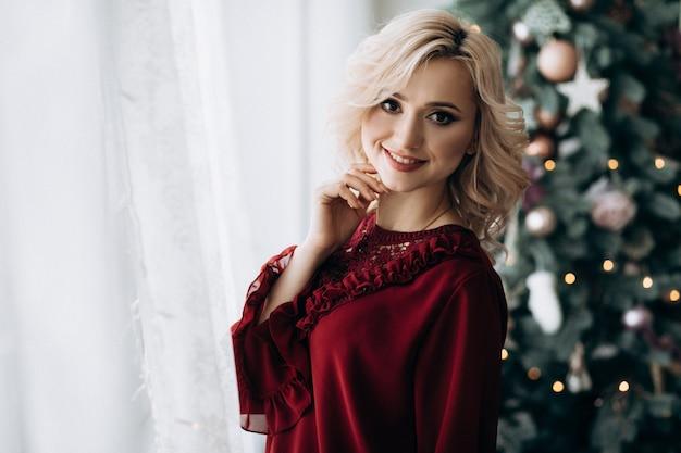 Fantasia mulher loira vestida em roupas vermelhas fica em uma sala com uma decoração de natal