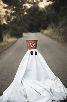 Fantasma com caixa de pipoca na cabeça sentado na estrada rural
