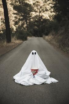 Fantasma com caixa de pipoca sentado na estrada rural