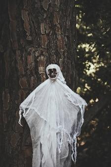 Fantasma com cara de caveira pendurado na árvore