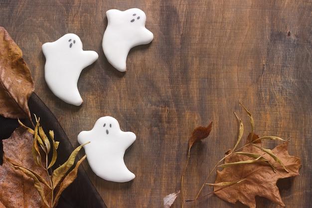 Fantasma de gengibre para o halloween, decorado com folhas de outono, sobre um fundo de madeira.