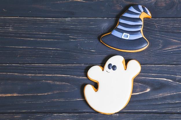 Fantasma de halloween com biscoitos de chapéu de bruxa na mesa