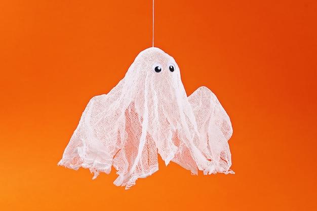 Fantasma de halloween de amido e gaze laranja. idéia do presente, decoração halloween. passo a passo