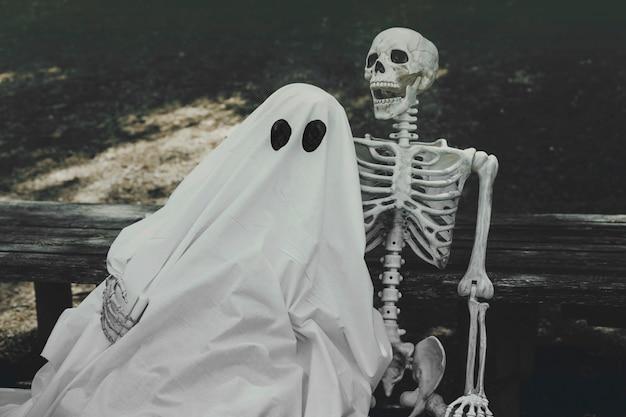Fantasma e esqueleto abraçando no banco