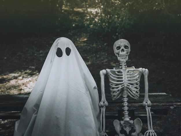 Fantasma e esqueleto sentado no banco no parque