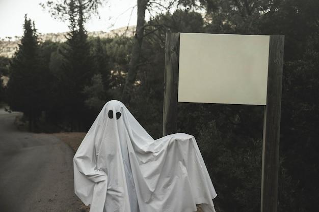 Fantasma em pé perto de placa de sinal colocada na estrada