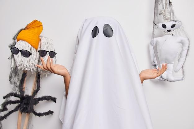 Fantasma feminina desconhecida cônica com lençol branco espalha as palmas das mãos com hesitação tenta parecer assustador usa fantasia de fantasma celebra poses de halloween em ambientes fechados. celebração de festa e conceito de mistério.