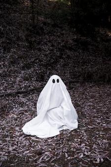 Fantasma sentado no solo na floresta