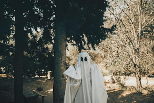 Fantasma sombrio em pé na floresta ensolarada