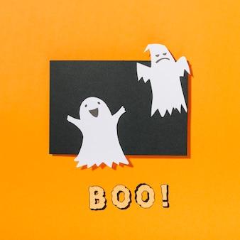 Fantasmas de halloween em pedaço de papel preto com boo! inscrição abaixo
